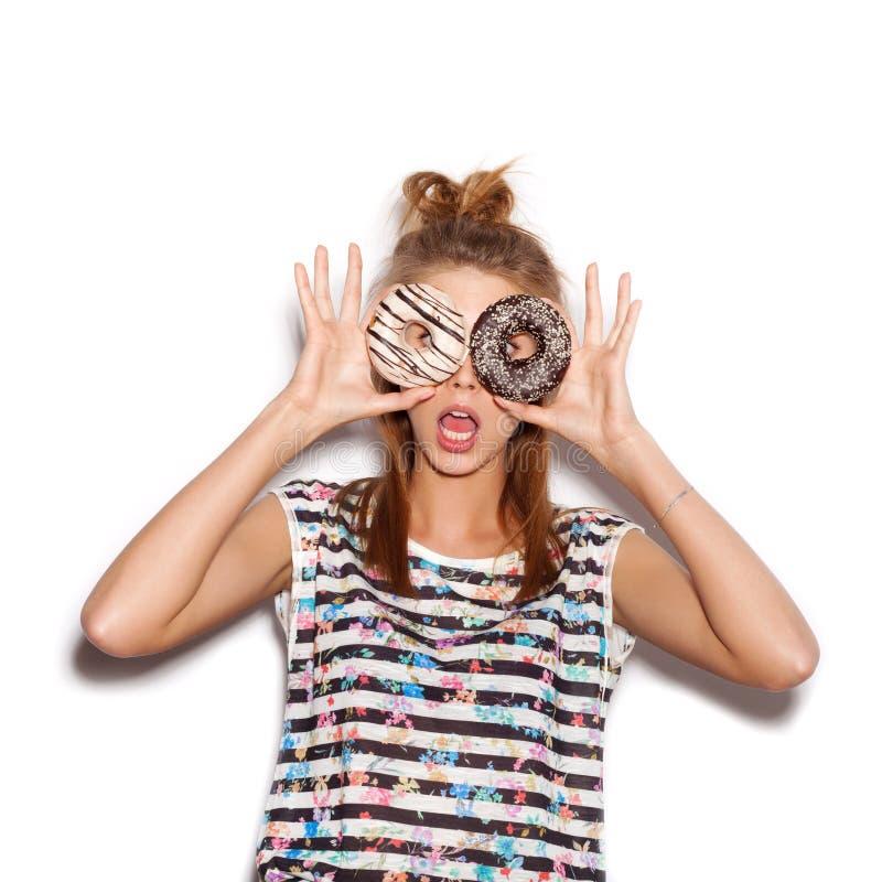 Hållande donuts för skämtsam flicka på hennes ögon royaltyfri fotografi