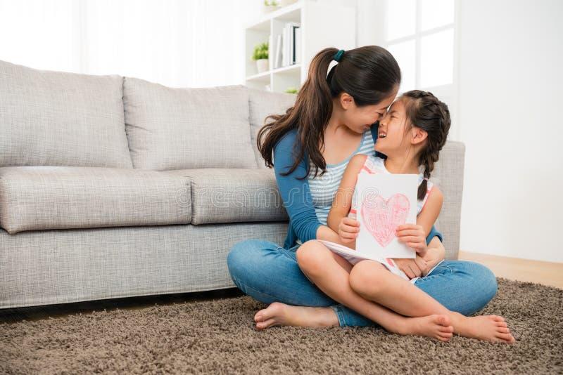 Hållande dotter för lycklig mamma och ge hennes kyss royaltyfri bild