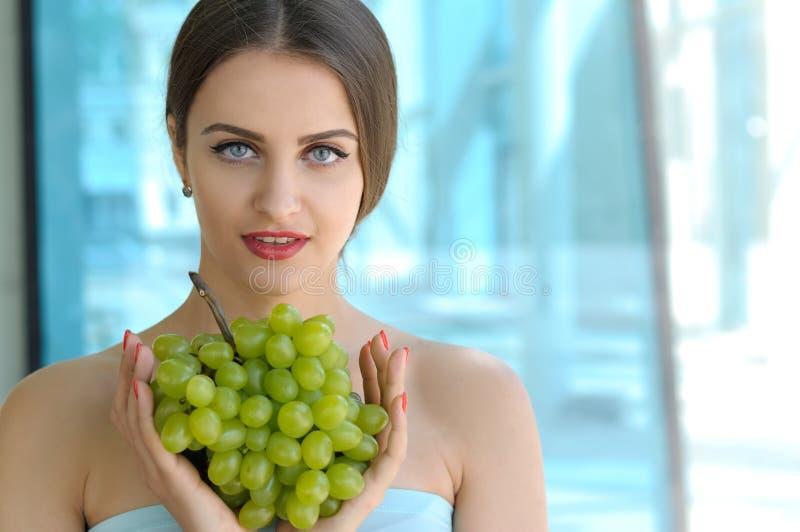 Hållande druvor för flicka som är främsta av bröstkorg fotografering för bildbyråer