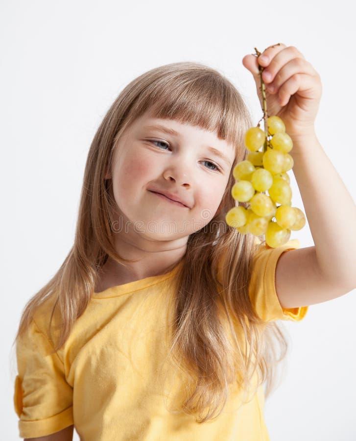 Hållande druvor för lycklig liten flicka arkivbild