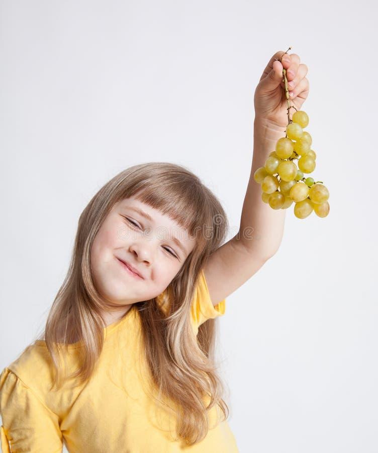 Hållande druvor för lycklig liten flicka fotografering för bildbyråer