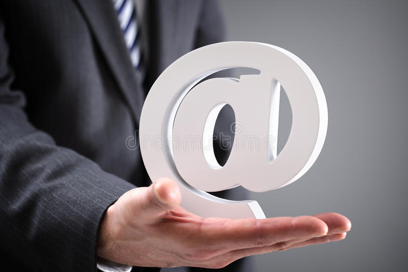 Hållande email för affärsman på symbolet royaltyfria foton