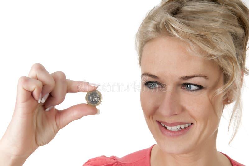 Hållande euromynt för kvinna mellan två fingrar arkivbild