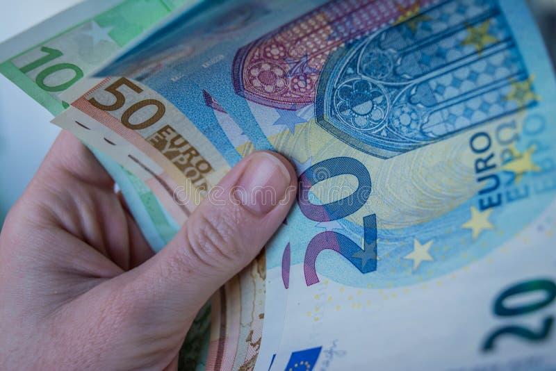 Hållande eurosedlar för kvinnlig hand royaltyfri foto