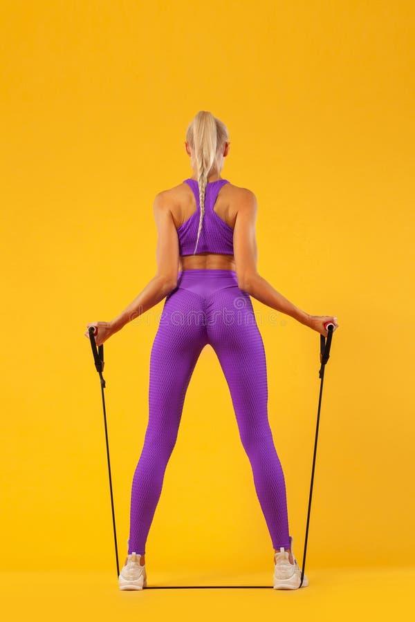 Hållande expander för för konditionkvinnaidrottsman nen och kroppsbyggare Isolerat på gul bakgrund royaltyfria foton