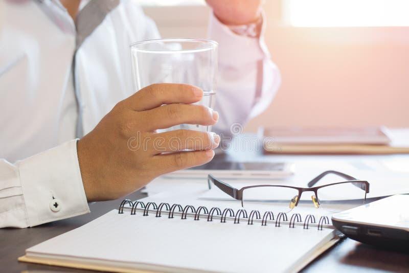 hållande exponeringsglas för affärsman av vatten och borttaexponeringsglas på tabellen royaltyfri bild