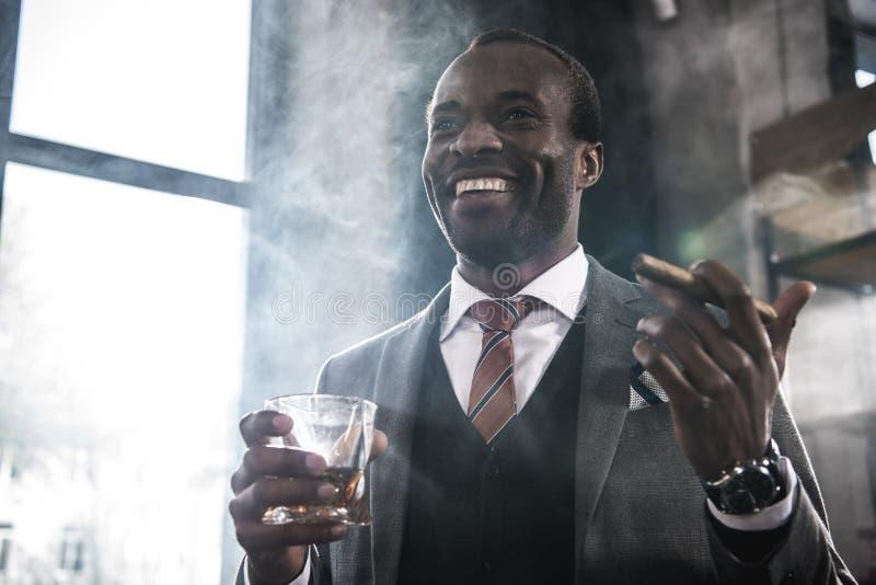 Hållande exponeringsglas för afrikansk amerikanaffärsman med whisky och rökacigarren royaltyfri fotografi