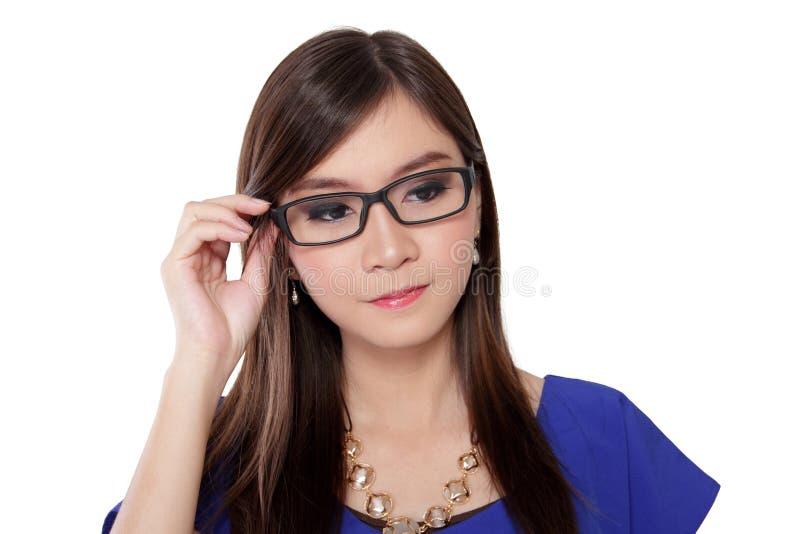 Hållande exponeringsglas för asiatisk kvinna som bort ser royaltyfri foto