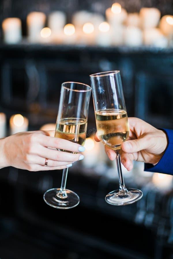 Hållande exponeringsglas för brud och för brudgum med champaign royaltyfria bilder