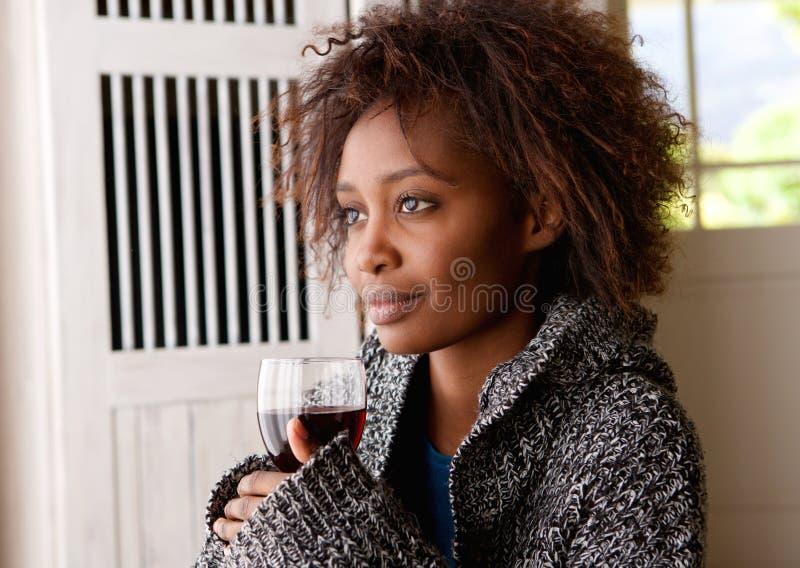 Hållande exponeringsglas för härlig afrikansk kvinna av vin royaltyfria bilder