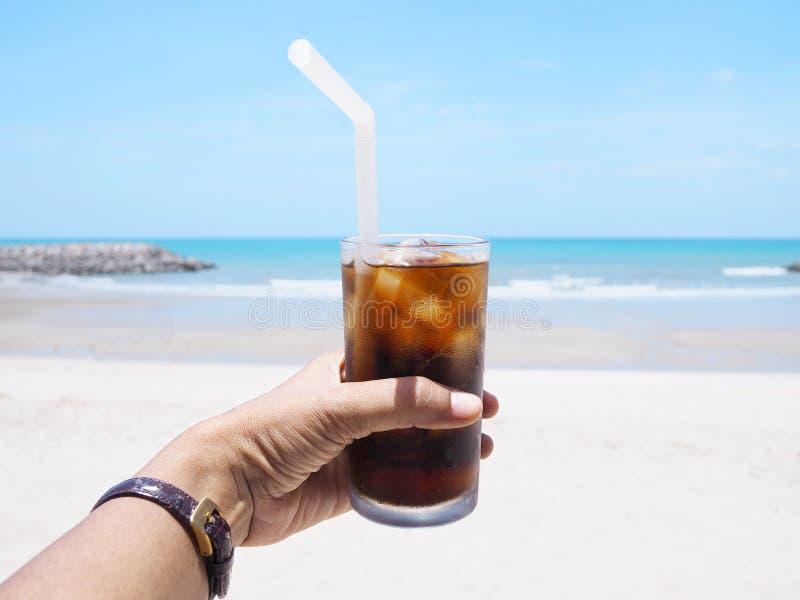 Hållande exponeringsglas för hand av läsken på stranden royaltyfri foto