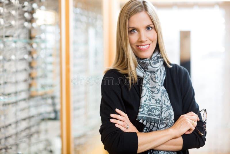 Hållande exponeringsglas för kvinna i optiker Store arkivfoton