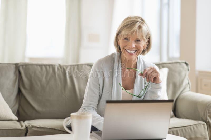 Hållande exponeringsglas för kvinna, medan genom att använda bärbara datorn i vardagsrum royaltyfria bilder