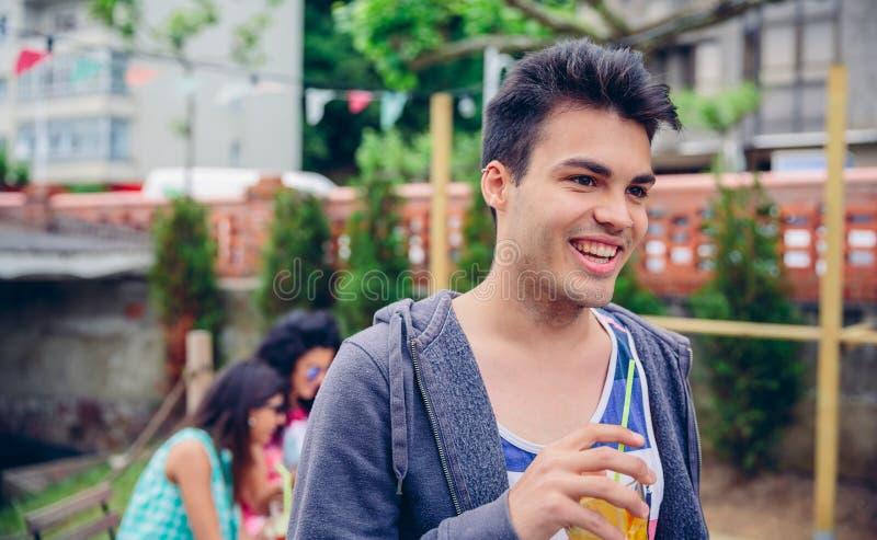 Hållande exponeringsglas för ung man av den ingav vattencoctailen utomhus royaltyfria foton