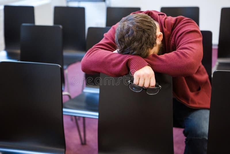 Hållande exponeringsglas för utmattad pojke och sova i mötesrum royaltyfria bilder