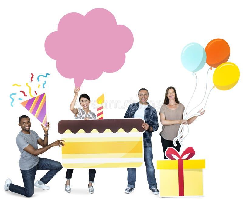 Hållande födelsedagkaka för lyckligt olikt folk royaltyfri bild