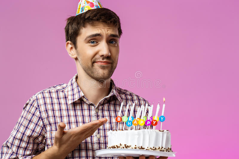 Hållande födelsedagkaka för uppriven man med en att inte blåsa ut stearinljuset royaltyfria bilder