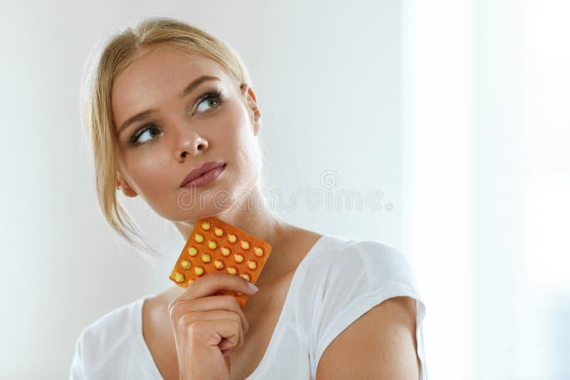 Hållande födelsekontrollpreventivpillerar för härlig kvinna, muntlig preventivmedel royaltyfri bild