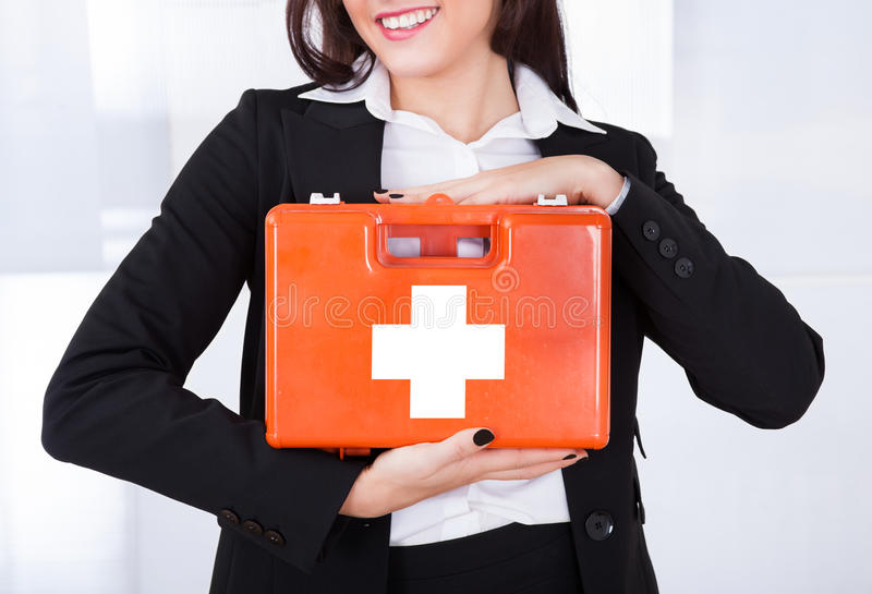 Hållande första hjälpenask för affärskvinna arkivfoto