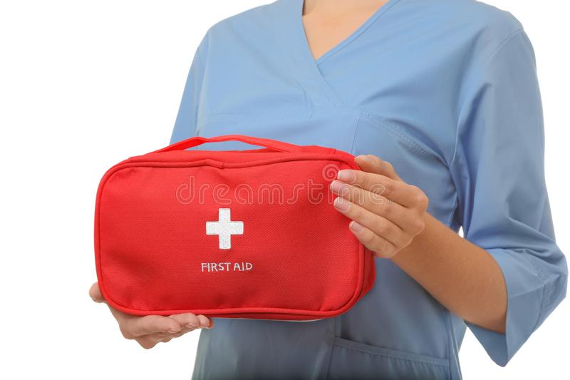 Hållande första hjälpensats för kvinnlig doktor på vit bakgrund, closeup fotografering för bildbyråer