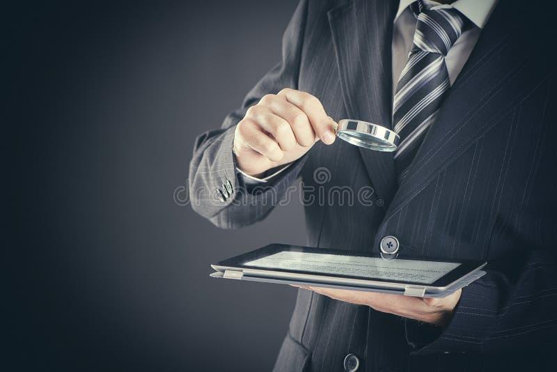 Hållande förstoringsglas för affärsman och digital minnestavla på mörkt för sökande och undersökabegrepp för bakgrund, royaltyfri foto