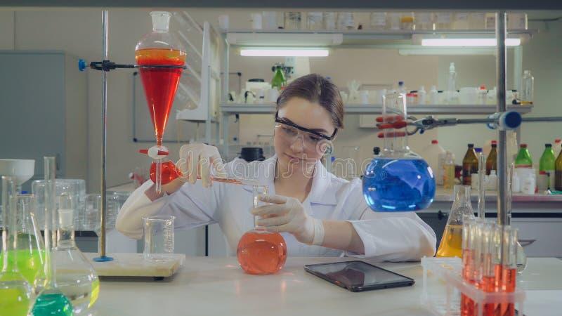 Hållande flaska för attraktiv yrkesmässig forskare i labb arkivbilder