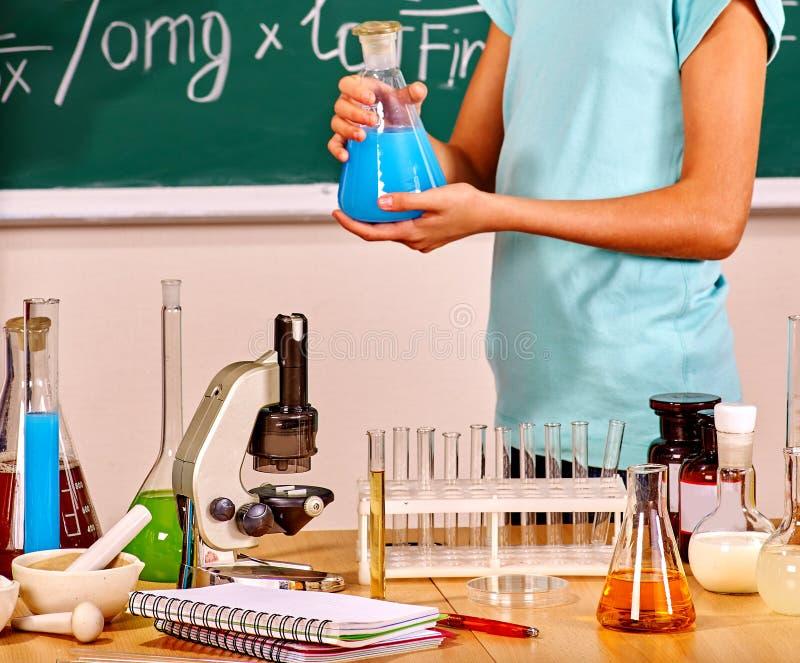 Hållande flaska för ungehand i kemigrupp fotografering för bildbyråer