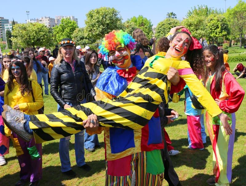 Hållande flickaclown för oidentifierad lycklig clown och posera på den orange blomningkarnevalet fotografering för bildbyråer