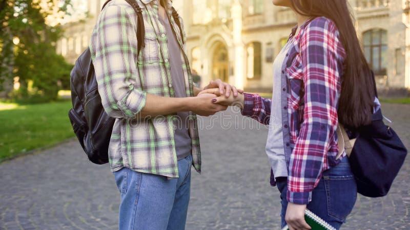 Hållande flickvänhand för ung man ömt, studentförälskelse, möte på broms royaltyfri fotografi