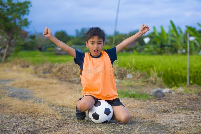 Hållande fotbollboll för stilig och lycklig ung pojke som utomhus spelar fotboll på att le för fält för grönt gräs som är gladlyn arkivfoto