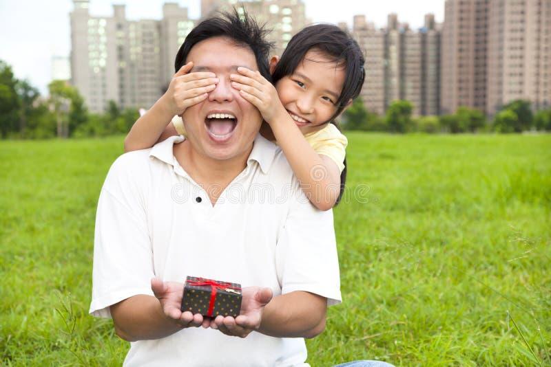 Hållande gåvaask för förvånad fader från liten flicka arkivbilder