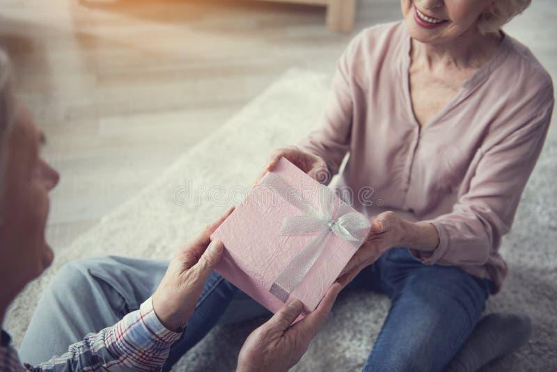 Hållande gåvaask för gamal man och för kvinna med glädje fotografering för bildbyråer