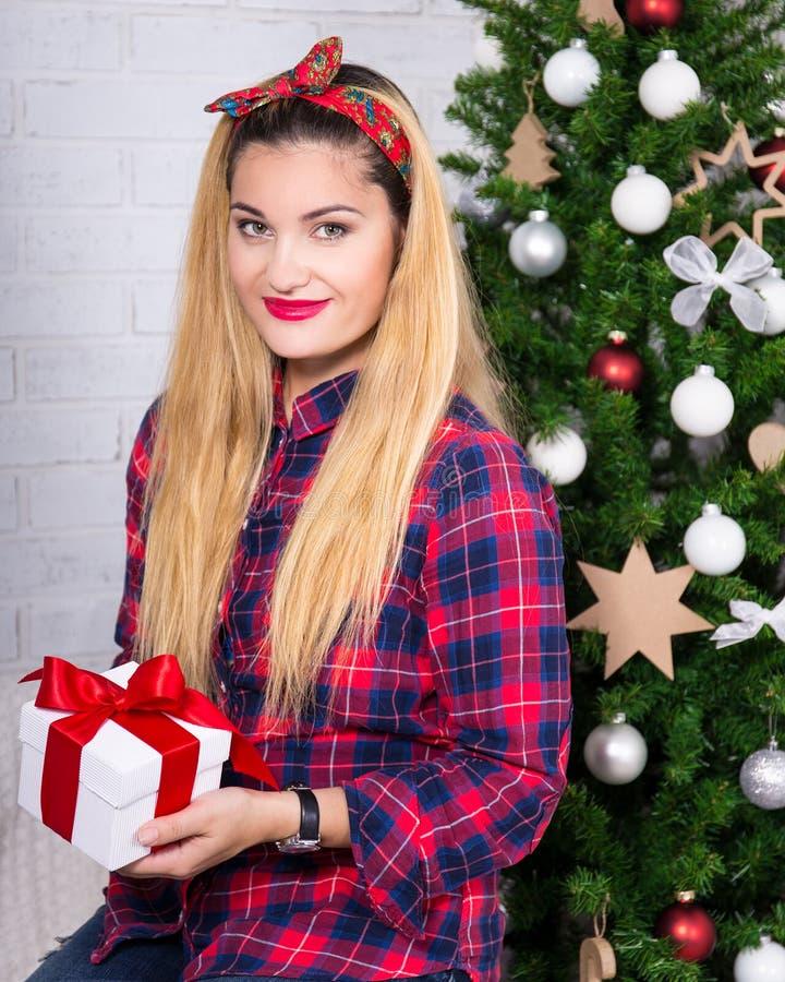 Hållande gåvaask för ung kvinna med den dekorerade julgranen royaltyfria bilder