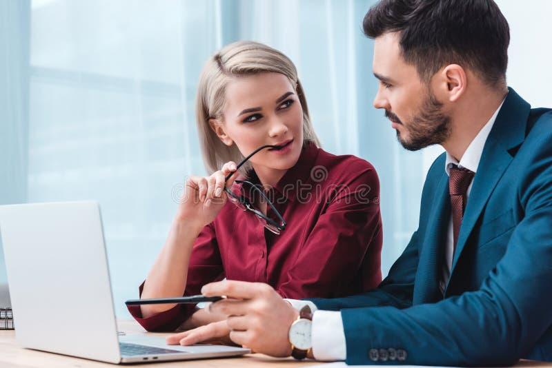 hållande glasögon för yiungaffärskvinna och flörta med den stiliga manliga kollegan arkivbild