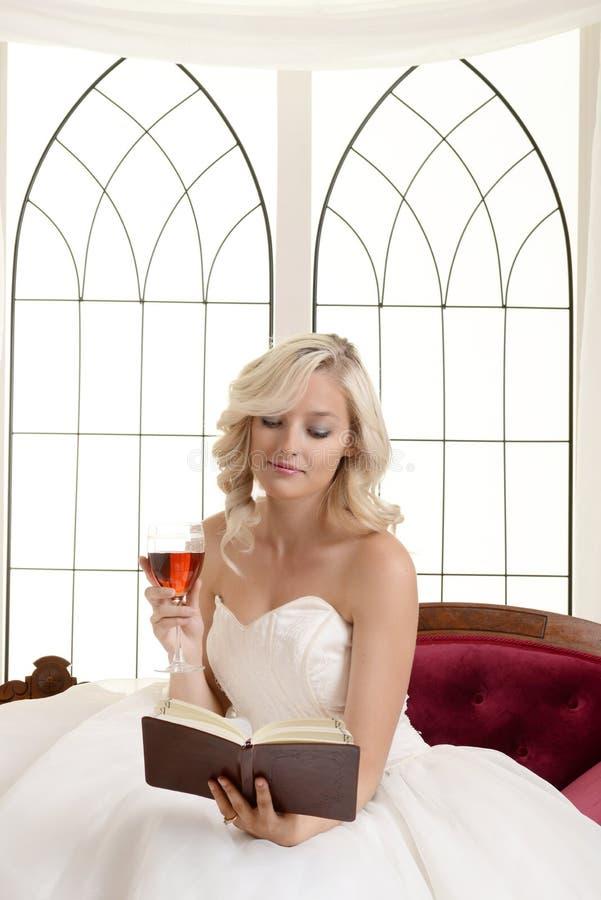 Hållande glass rött vin för kvinnaläsebok arkivbilder