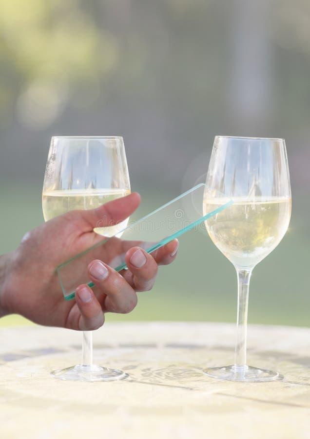 Hållande glass skärm för hand med två exponeringsglas av champagne och solig grönska arkivfoton