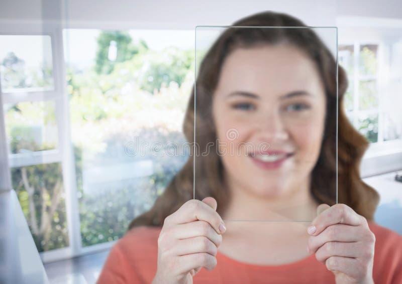 Hållande glass skärm för kvinna vid det soliga fönstret fotografering för bildbyråer