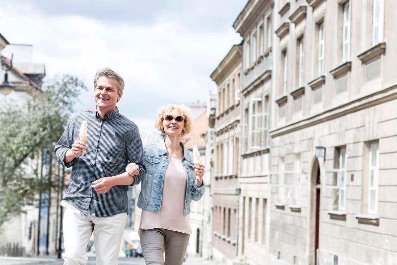 Hållande glasskottar för lyckliga medelåldersa par, medan gå i stad royaltyfria bilder