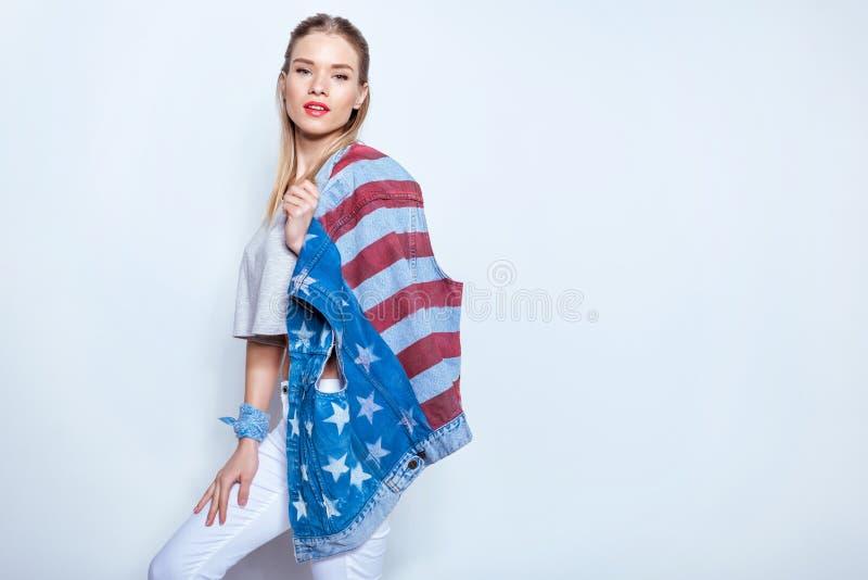 Hållande grov bomullstvillväst för blond flicka med amerikanska flaggan på skuldra och se kameran arkivfoto