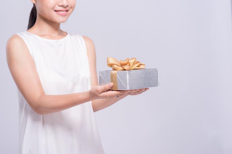 Hållande guld- gåvaask för härlig asiatisk kvinna på vit bakgrund arkivbild