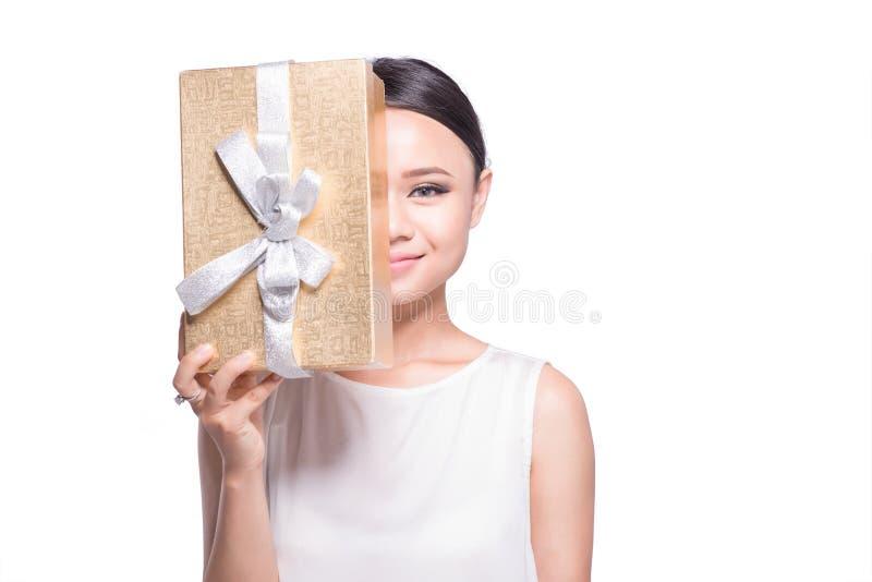 Hållande guld- gåvaask för härlig asiatisk kvinna på vit bakgrund royaltyfri fotografi