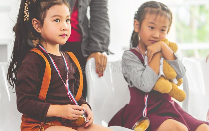 Hållande guldmedalj för liten flicka för studentutmärkelse royaltyfri bild
