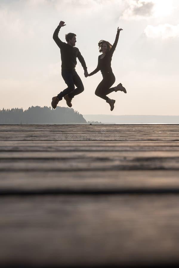 Hållande händer för unga par som hoppar i luften fotografering för bildbyråer