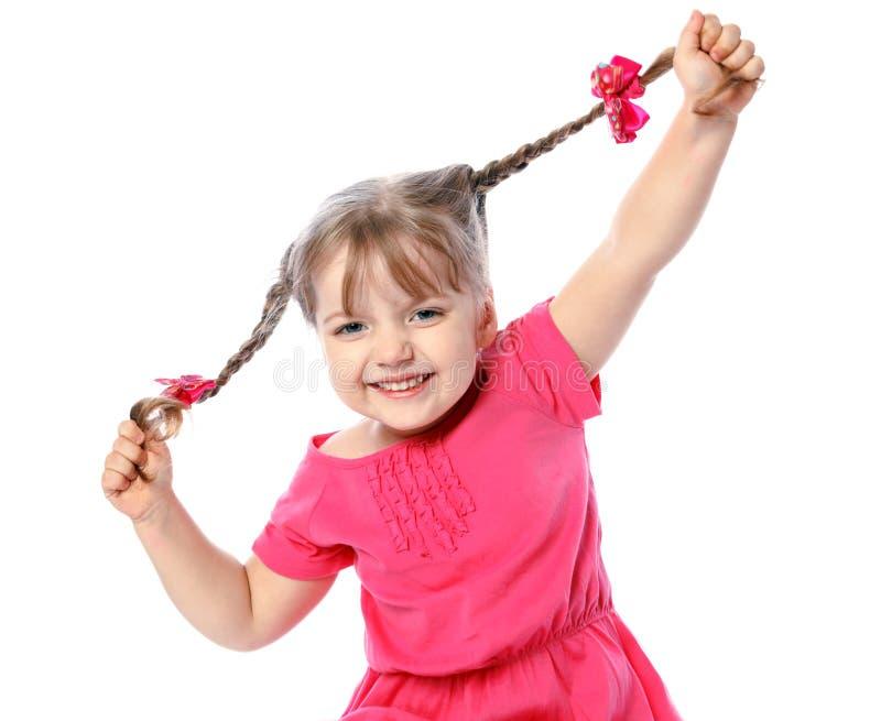 Hållande hår för liten gladlynt flicka royaltyfri fotografi