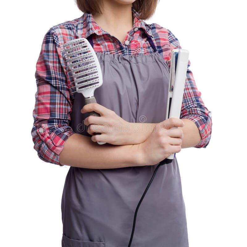 Hållande hårstraightener för lycklig frisör på vit backgropund royaltyfri foto