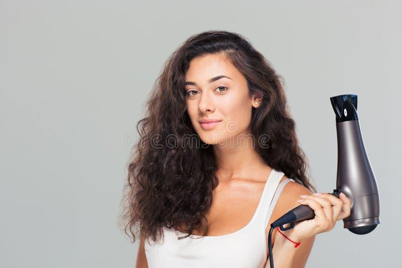 Hållande hairdrye för gullig attraktiv kvinna royaltyfri foto