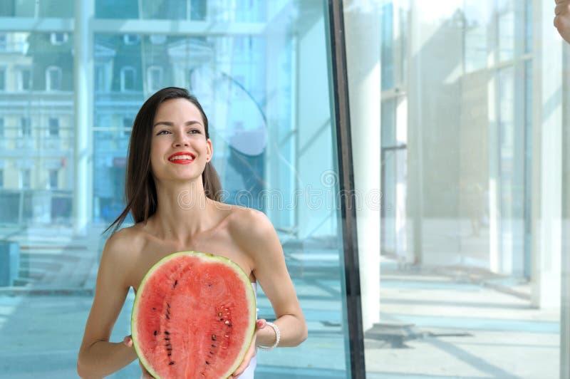 Hållande halva för härlig flicka av vattenmelon royaltyfria bilder