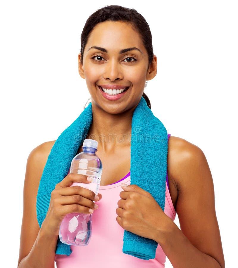 Hållande handduk för färdig kvinna och vattenflaska royaltyfri foto
