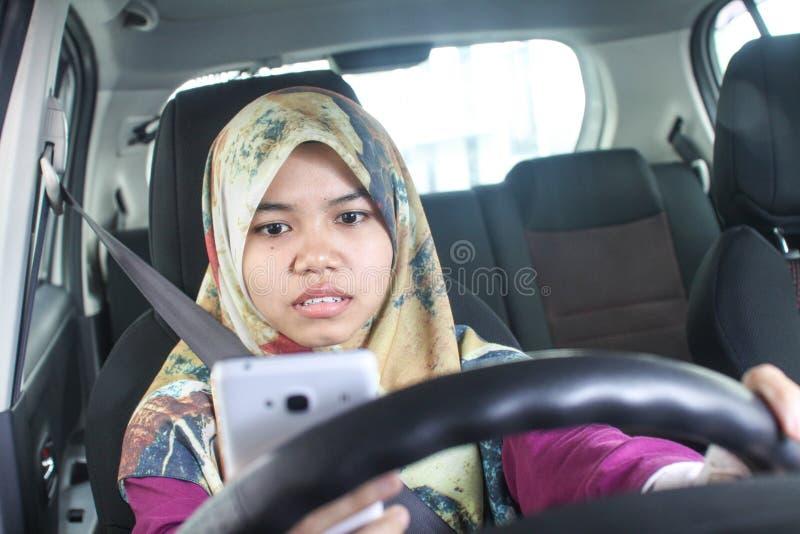 Hållande handphone för muslimsk kvinna, medan köra royaltyfri fotografi