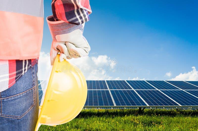Hållande hardhat för tekniker på tillbaka photovoltaic paneler för solenergi royaltyfri fotografi